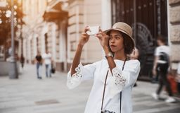 Menina brasileira que fotografa na rua através de seu smartphone foto de stock royalty free