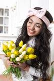 Menina brilhante com um sorriso na cozinha com as tulipas amarelas de а na cozinha foto de stock royalty free