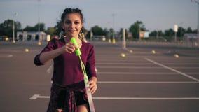 Menina brincalhão nova do moderno com as tranças longas que fundem bolhas no estacionamento pela alameda da cidade durante o por  video estoque