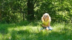 Menina brincalhão que aprecia o tempo morno do verão fora no parque durante Sunny Day Criança fêmea que pegara o verde vídeos de arquivo