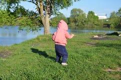 A menina brincalh?o bonito de sorriso est? estando na grama verde a menina que a crian?a anda em torno do lago aprende andar enso imagens de stock