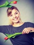 Menina brincalhão que tem o divertimento com tulipas das flores Imagem de Stock Royalty Free