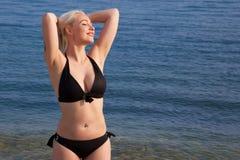 A menina bronzea-se no Sun na praia Foto de Stock Royalty Free