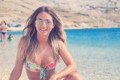 Menina bronzeada bonita em um biquini que senta-se em uma praia rochosa Fotos de Stock