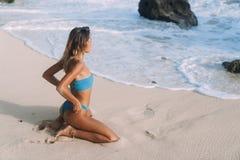 A menina bronzeada com corpo desportivo no roupa de banho senta-se no Sandy Beach e nos olhares no oceano e nas ondas fotos de stock royalty free