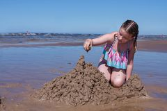 A menina bulding castelos de areia na praia imagem de stock