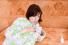 A menina caiu doente e bebe o chá Foto de Stock Royalty Free