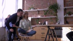 Menina calma nova do trabalhador de escritório que relaxa e que medita no local de trabalho que senta-se na pose da ioga com os o filme
