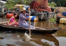 Menina cambojana que viaja pelo barco no lago sap de Tonle Fotos de Stock Royalty Free