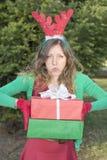 Menina cansado com as orelhas da rena que guardam presentes de Natal Foto de Stock Royalty Free
