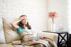 A menina cansado da virada infeliz está sentando-se em um sofá em casa que sofre imagem de stock royalty free