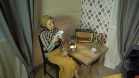 A menina cansado do alfaiate tem um resto, chá das bebidas, relaxa, escuta música na placa, no gramofone ou no fonógrafo do vinil filme
