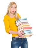 Menina cansado do estudante que guardara a pilha dos livros foto de stock