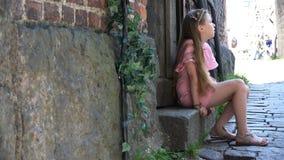Menina cansado que senta-se pela porta de madeira na etapa filme