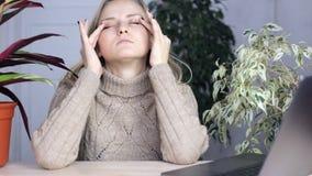 A menina cansado que tenta ajustar dentro para trabalhar e fricciona seus olhos vídeos de arquivo