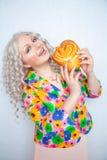 A menina carnudo bonito com cabelo encaracolado branco em um revestimento do verão com flores guarda um bolo doce da pastelaria n fotografia de stock