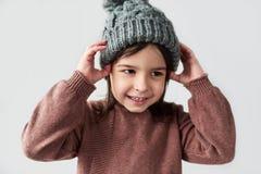 Menina caucasiano alegre na camiseta cinzenta morna do chapéu do inverno, do sorriso e vestir isolada em um fundo branco do estúd imagem de stock royalty free