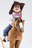 Menina caucasiano alegre pequena na roupa da vaqueira que monta Toy Horse Imagem de Stock Royalty Free