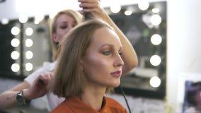 A menina caucasiano atrativa com compõe no salão de beleza O cabeleireiro endireita seu cabelo com um ferro borrado vídeos de arquivo