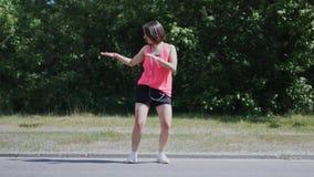 Menina caucasiano atrativa na camisa cor-de-rosa com os fones de ouvido que dançam no parque Jovem mulher que faz movimentos engr filme