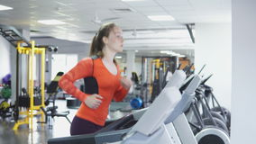 Menina caucasiano atrativa que corre na escada rolante no gym do esporte, 4k