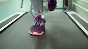 Menina caucasiano atrativa que corre na escada rolante no gym do esporte Pés do close-up video estoque