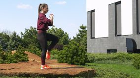 Menina caucasiano bonita atlética magro que faz exercícios da aptidão na natureza A mulher bonita faz o salto com investe contra  video estoque