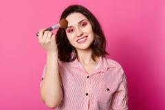 Menina caucasiano bonita com pó applaying da composição brilhante usando a escova, poses fêmeas atrativas sorriso, olhando direta imagem de stock royalty free