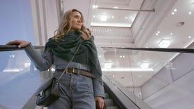 Menina caucasiano bonita em um casaco azul e em um lenço verde, sorriso, indo abaixo da escada rolante em um shopping video estoque