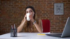 A menina caucasiano bonita está bebendo do copo do Livro Branco e está tendo a conversa telefônica ao ficar no desktop video estoque