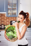 Menina caucasiano bonita no desgaste desportivo que guarda a cesta de legumes frescos e de pepino das mordidas Imagem de Stock Royalty Free