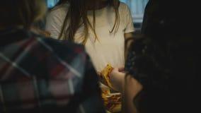 Menina caucasiano bonita nova que come a pizza com amigos em uma tabela da barra da cozinha em uma festa em casa ocasional do div vídeos de arquivo