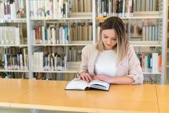 Menina caucasiano bonita nova que lê um livro na biblioteca fotos de stock