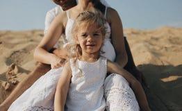 A menina caucasiano bonita pequena que está entre seus pés dos pais Matriz grávida Família feliz na roupa do whote fotografia de stock