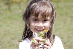 Menina caucasiano bonita que joga com uma flor Foto de Stock