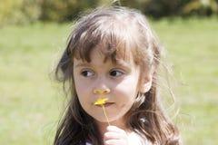 Menina caucasiano bonita que joga com uma flor Fotos de Stock