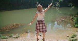 Menina caucasiano bonita que passa o tempo por um lago no madeiras vídeos de arquivo