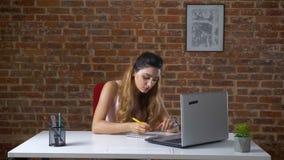 A menina caucasiano bonito com cabelo encaracolado longo está sentando-se no desktop e está escrevendo-se para baixo notas de seu filme