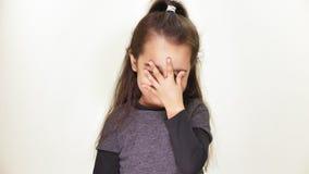 Menina caucasiano bonito pequena que olha a câmera, sorrindo, fazendo o facepalm, mostrando a emoção da decepção, retrato vídeos de arquivo