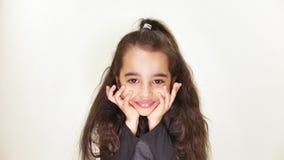 Menina caucasiano bonito pequena, sorrindo, mostrando uma emoção da expectativa, guardando sua cabeça com suas mãos, branco do re video estoque
