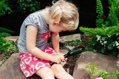 a menina caucasiano branca adorável bonito que olha plantas floresce a begônia através da lupa Fotos de Stock Royalty Free