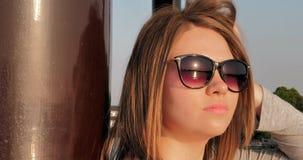 Menina caucasiano consideravelmente nova nos vidros que estão na coluna no por do sol filme