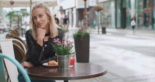 Menina caucasiano consideravelmente nova que senta-se no café e que sorri a uma câmera vídeos de arquivo