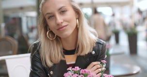 Menina caucasiano consideravelmente nova que senta-se no café e que sorri a uma câmera filme