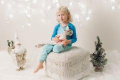 Menina caucasiano da criança com os olhos azuis que sentam-se com brinquedos que comemora o feriado do Natal ou do ano novo Fotografia de Stock Royalty Free