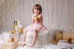 Menina caucasiano da criança com os olhos azuis que sentam-se com brinquedos que comemora o feriado do Natal ou do ano novo Imagem de Stock Royalty Free