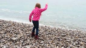 Menina caucasiano da criança que joga na praia vazia filme