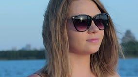 Menina caucasiano de sorriso bonita posta sobre seus óculos de sol no por do sol, fundo blured filme