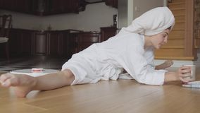 Menina caucasiano flexível nova alegre após um chuveiro em um roupão que senta-se na guita que lê um café das bebidas do comparti filme