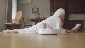 Menina caucasiano flexível nova bonito após um chuveiro em um roupão que senta-se na guita que lê bebidas café ou chá de um compa filme